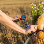 Close up of woman hand's driving bicycle with basket full of fresh camomile and bread